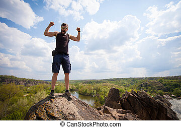 Young man stands on the top of rock