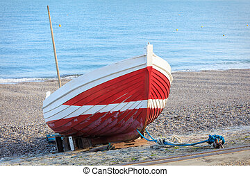 Boat at the beach - seaside shot Red boat on the pebble...
