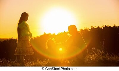 Happy Mother Dancing With Children At Sunset