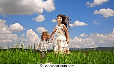 Girl And Boy Jumping In Green Field