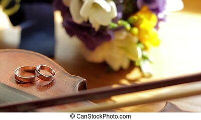 Wedding rings are on the violin Violin lying on the table...
