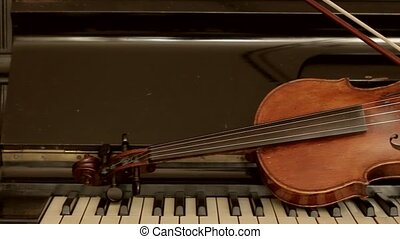 Old violin lying on the piano Still life of violin and piano...