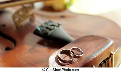 Panorama of the old violin. Wedding rings on the old violin....