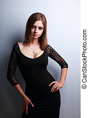 Beautiful figure woman with big bust posing in black dress...