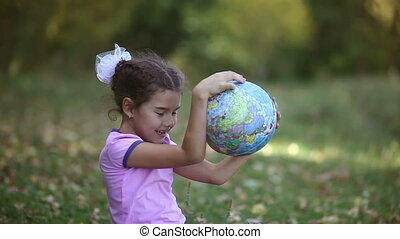 teen girl sitting green  grass playing studying Globe happy
