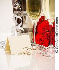 Wedding rings with writing card and champagne, close up