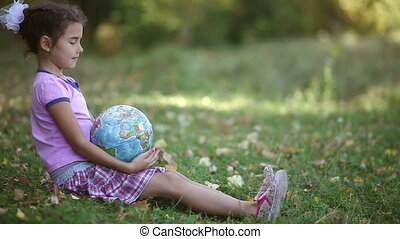 teen brunette girl sitting on green grass playing studying Globe happy