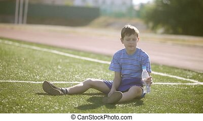 Boy teenager tired football athlete drinks water from a plastic bottle sits on a grass sports