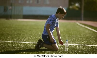 Boy teenager tired football athlete drinks water from plastic bottle sits on a grass sports