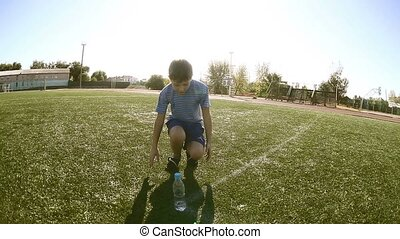 Boy tired football teenager athlete drinks water from plastic bottle sits on a grass sports