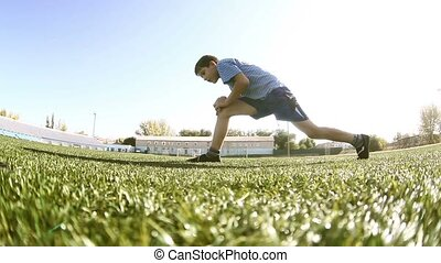 Teenage doing boy workout footballer athlete sits on a grass...