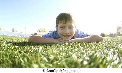 teenager boy lying on the grass smiling happy childhood summers