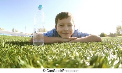 Teenage drinking boy water from a plastic bottle lying on...