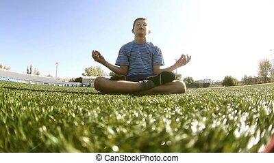 teenager sitting boy meditating yoga stadium grass green...