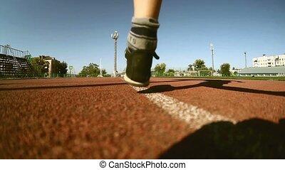 Teen athlete boy runner running on the treadmill stadium sun sunny day healthy lifestyle