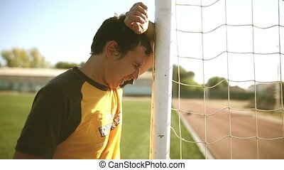 football man upset defeat shouts knocks on the goal post...