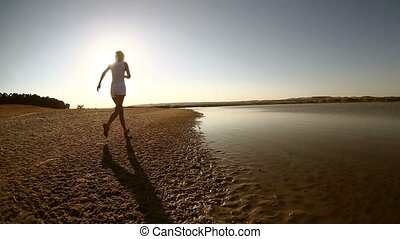 woman runs along the beach girl healthy lifestyle athlete...