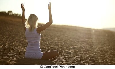 woman in white sitting on sand meditation healthy lifestyle sunset the sun goes down, silhouetted against the sky Yoga