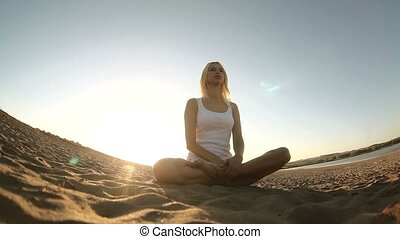 woman in white sitting on sand meditation healthy lifestyle sunset sun goes down, silhouetted against the sky Yoga