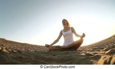 woman in white sitting on the sand meditation healthy...