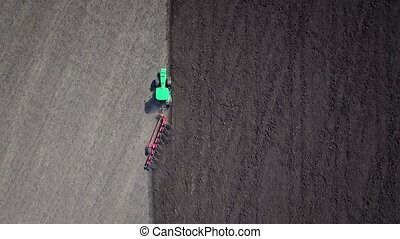 Aerial: Tractor plowing the soil.