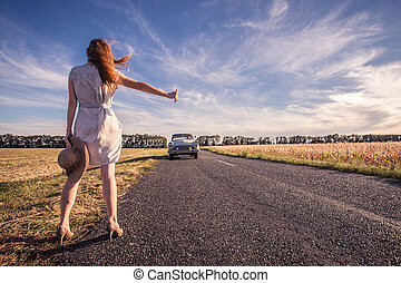 hitch-hike - young woman hitch-hiking on a road at the...