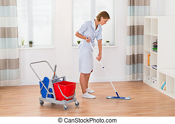 Female Housekeeper Cleaning Floor With Mop - Young Female...