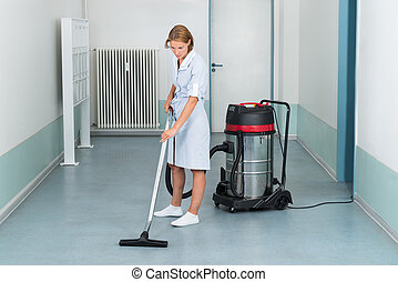 Female Cleaner Vacuuming Floor - Young Female Cleaner In...