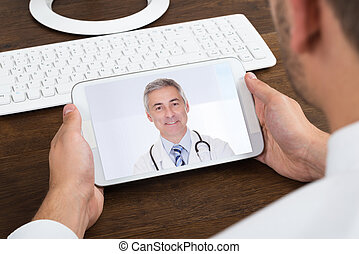 Businessperson Videochatting With Senior Doctor - Close-up...