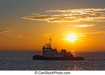 Silhouette of a tug boat at sunset