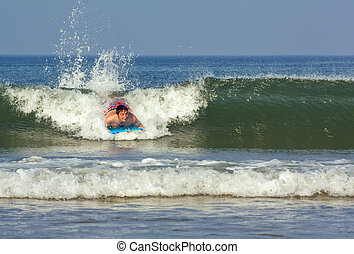 Young man on a boogie board - Young man rides a wave on a...