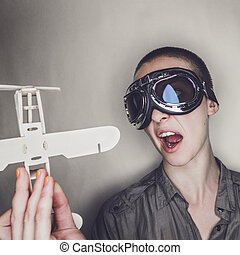 girl in retro pilot glasses with wooden plane - short-haired...