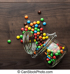 overturned glass jar full of colorful sweets - topple over...