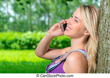 blonde girl on the phone leaning against a tree