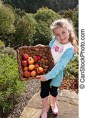 Young girl with basket of fruit - Young girl posing with a...