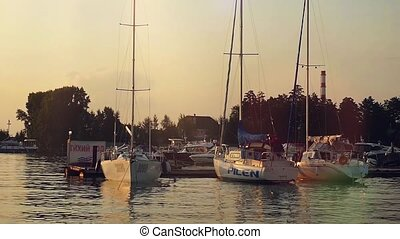 View on Sea bay with yachts at sunset at a wharf and Pier on the foreground in slowmotion. Panorama