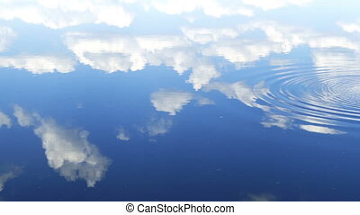circles flow along surface of water, in water reflects sky...