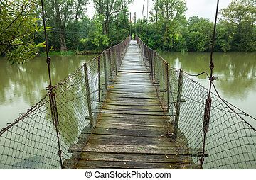 Suspension walking bridge - Rickety foot bridge over muddy...
