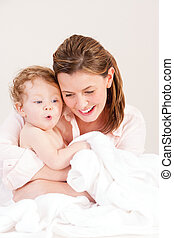 Baby Bath Time - Mother playing with her baby daughter after...