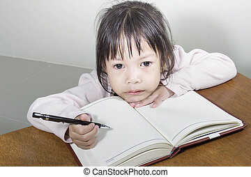 Asian girl kid hard at work in the room sitting with his...