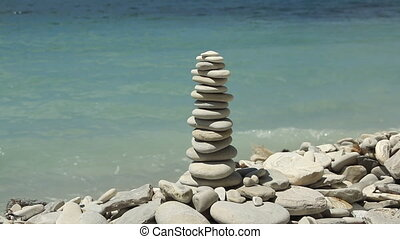 stack of zen stones on the beach at sunny day