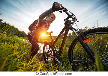 Cycling - Lady with bicycle moving through lush meadow at...