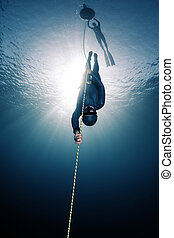 Freedivers - Lady free diver descending along the rope...