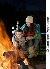 mother and son on bonfire night - Little boy is sitting with...