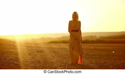 Young seductive woman woman walking through the desert sand...