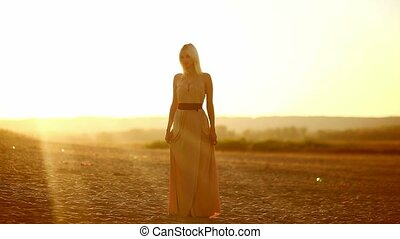 Young seductive woman blonde woman on sunset silhouette of a...