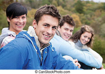 Four friends sit together outdoors and smile for the camera