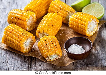 Grilled sweet corn with salt and lime on wooden table