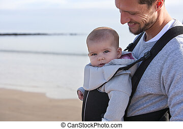 Father and Baby - Father carrying his baby daughter on his...