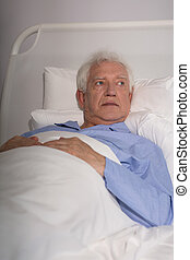 Elder man in hospital bed - Close-up of an old man lying in...
